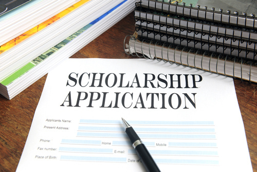 A scholarship application and pen surrounded by books and notebooks.