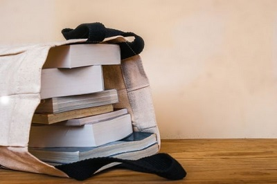 A white canvas book bag filled with books.