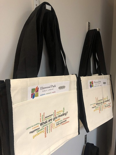Hanging Elmwood Park Public Library canvas tote bags that are available for checkout.
