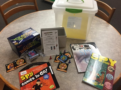 Contents of the Super Spy themed Explore-to-Go Kit, including a books and game.